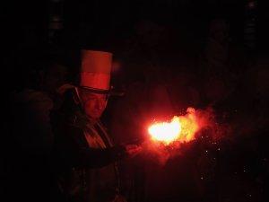 Senji látnivalók, kalapos férfi égő pálcát tart a karneválon